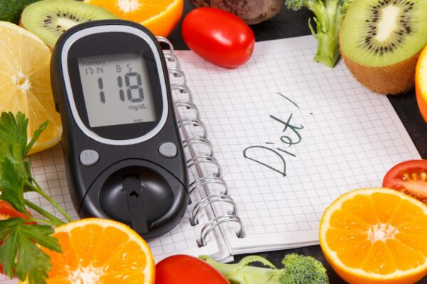 Glucometer with result of sugar level, fruits with vegetables and notepad with word diet